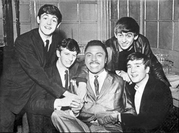 A black and white photo of the Beatles surrounding Little Richard in 1963.