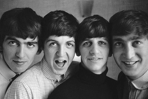 A black and white photo of the Beatles shot from mid-chest up, with their heads all pressed together side by side. From left to right, George diverts his eyes from the camera and smirks, Paul makes a surprised face, Ringo gives a small smile, and John grins broadly.