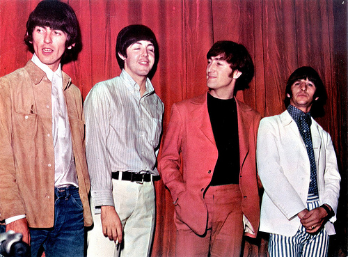 The Beatles in 1866, standing in front of a pinkish-red curtain. From left to right, George Harrison wears jeans, a white shirt, and light brown jacket and looks off to the side; Paul McCartney wears white pants and stripped buttoned up shirt, while smiling with eyes closed; John Lennon wears a pinkish-red suit with black tee-shirt and looks at Paul; Ringo Starr wears blue and white striped pants, a blue and white polka dot shirt, and white blazer, and stares into the distance.