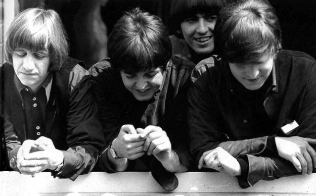 The Beatles in 1965, leaning out of a window during the filming of their movie Help! From left to right: Ringo rests will elbows on the window ledge, eyes closed; Paul also leans on the ledge and looks down and laughs heartily to himself; George stands behind the others and smiles widely; and John rests both arms on the sill and looks down at the ground below.