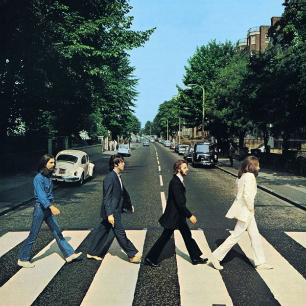 The cover of the Abbey Road LP. In the foreground, the four Beatles walk across a crosswalk. John leads, sporting long hair, a beard, and an all white suit. Ringo follows in a very formal, black suit with white shirt. Paul McCartney comes next, in a less formal blue suit, and bare feet. George Harrison in last, in sneakers, jeans, and a denim work shirt. In the background is the rest of the street, and a white Volkswagon Beetle.