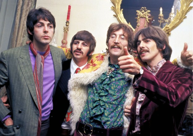 The Beatles stand in a line with their arms around each other in 1967, from left to right: Paul, Ringo, John, and George. Paul wears a gray suit jacket over a purple tee-shirt with a red and gray scarf, and stares off into space with one hand in his pocket. Ringo wears a black suit with white shirt and red patterned tie, and looks at someone off camera. John wears a turquoise shirt with a light green a purple pattern and ruffles going down the front, under a yellow jacket with a red floral pattern and white faux fur trip. He smiles and gives a thumbs up to someone off camera over George's shoulder. George wears a purple patterned shirt under a velvet striped purple striped jacket, and also gives a thumbs up. All except Paul have mustaches.