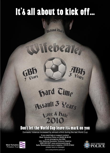 "A presumably white male stands with his back to the camera. On his back and neck are numerous tattoos that read ""behind bars,"" ""wifebeater,"" ""GBH 7 years,"" ""ABH 5 years,"" ""hard time,"" ""assault 3 years,"" and ""love & hate 2010."" A tattoo of a soccer ball is in the middle. The text on the poster reads ""It's all about to kick off ... Don't let the World Cup leave its mark on you."""