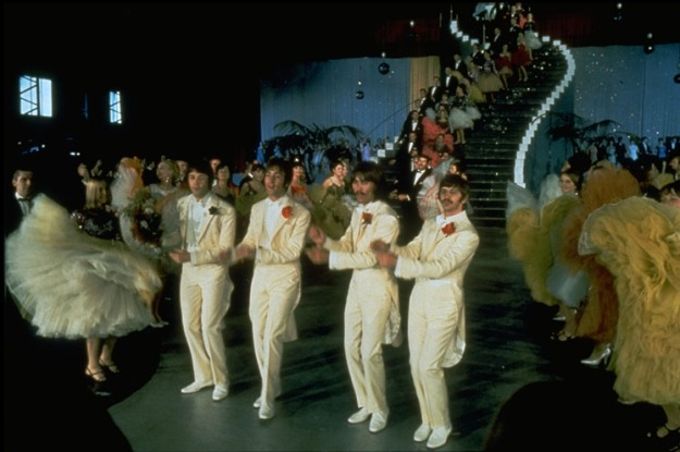 The Beatles dance a soft shoe shuffle in matching white tuxedos, in front of a long winding staircase filled with other dancers, and dancers swinging large skirts at either side. John, George, and Ringo all wear red carnations on their lapel. Paul wears a black carnation.