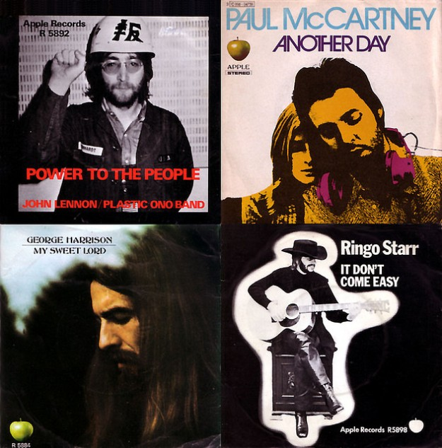 The picture sleeves from first singles from each of the four Beatles arranged in a two by two square. Clockwise from top left is John Lennon's Power to the People, which features a black and white photo of him wearing a hard hat with Japanese writing and doing a solidarity fist; Paul McCartney's Another Day, featuring a photo of him wearing headphones around his neck with Linda cuddled up to his shoulder; Ringo Starr's It Don't Come Easy, which features a black and white photo of Ringo wearing a cowboy hat and leather pants while playing an acoustic guitar; and George Harrison's My Sweet Lord, featuring a long-haired George looking down at the ground solemnly.