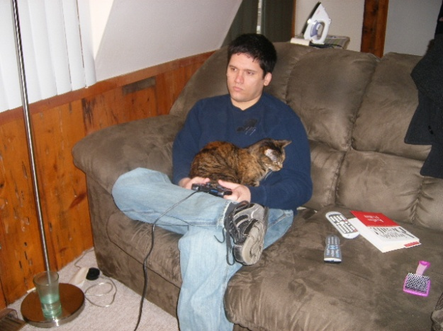 Ian sits on a couch holding a video game controller while Minks its on his lap.