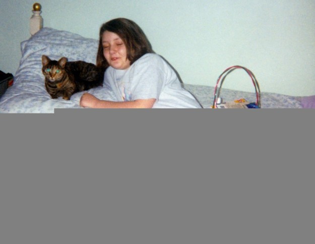 Me, a ten year old girl in purple leggings and white tee-shirt, on the bed with Mink, a brownish-tortoise shell cat, and an easter basket.