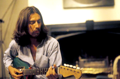 George Harison in 1969 with long hair and beard sits in the studio playing a guitar.