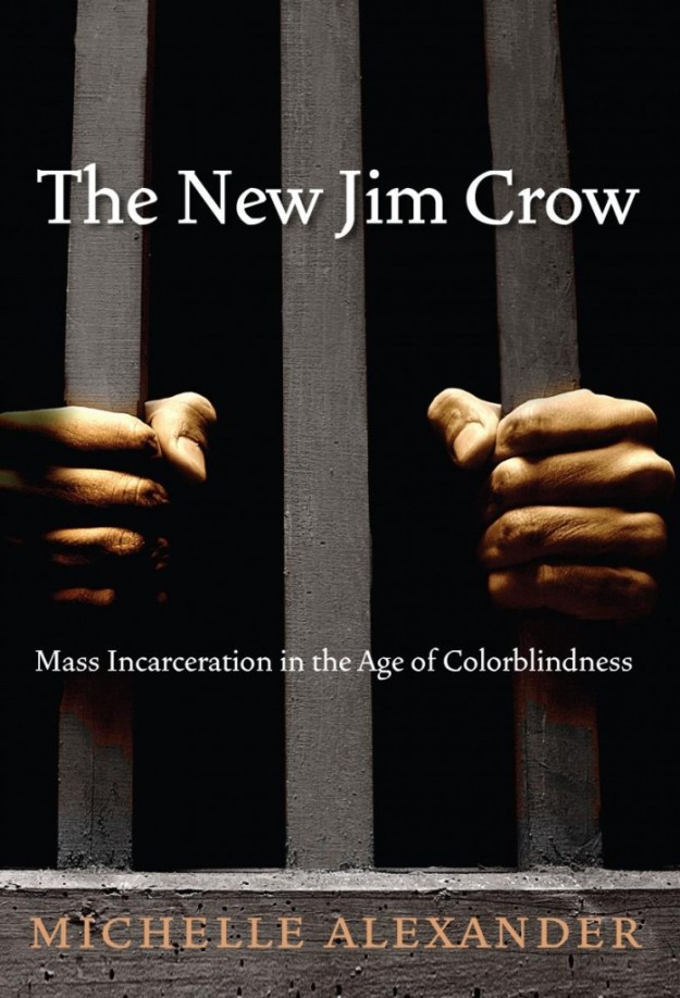 "The cover of the book ""The New Jim Crow"" by Michelle Alexander. A pair of Black hands grip vertical wooden bars against a dark background."