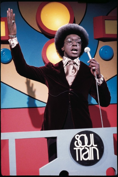 Don Cornelius stands with arms raised on the original 1970s Soul Train set