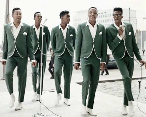 In matching green suits with no lapels, the Temptations pose on the sidewalk, with David Ruffin crooning dramatically into a microphone.
