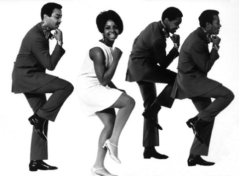 A black and white phot of Gladys Knight and the Pips demonstrating a dance move. Turned to the side, they each pump one arm down while raising the knee high up.
