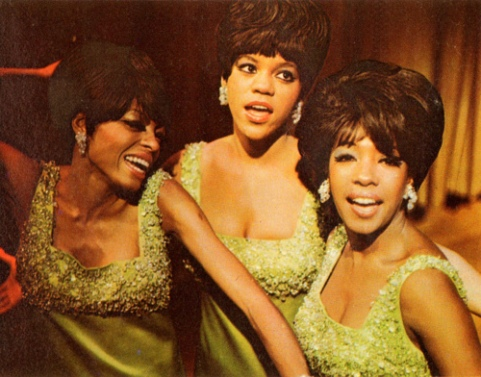 A close shot of The Supremes posing for the camera in glamorous hair and makeup and sparkling green gowns