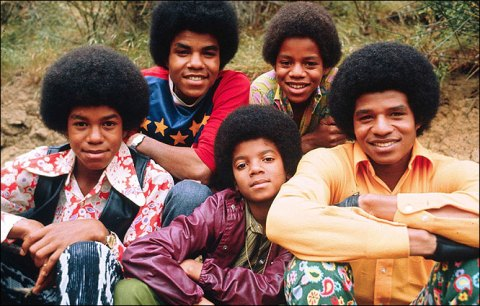 The Jackson 5 early in their career, sporting colorful 60s clothes and perfectly coifed afros, sit and pose for the camera.